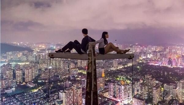 Man and woman sitting on top of building